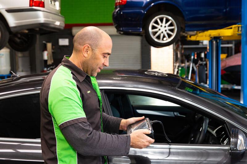 Noranda Service Centre Gallery Images - Car Checkup Using Gadget Closeup Mechanic Checking