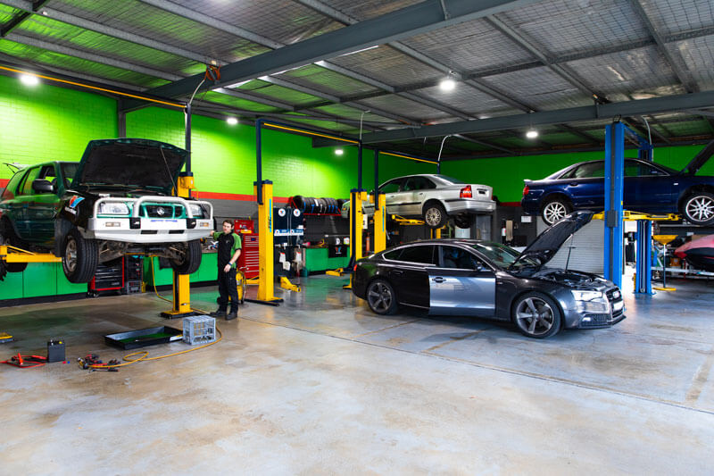 Noranda Service Centre Gallery Images - Car Mechanic Working on a Big Wide Workshop Car Raised