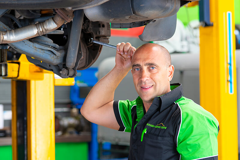Noranda Service Centre Gallery Images - Checking and Tightening of Car Parts Mechanic Looking at Camera