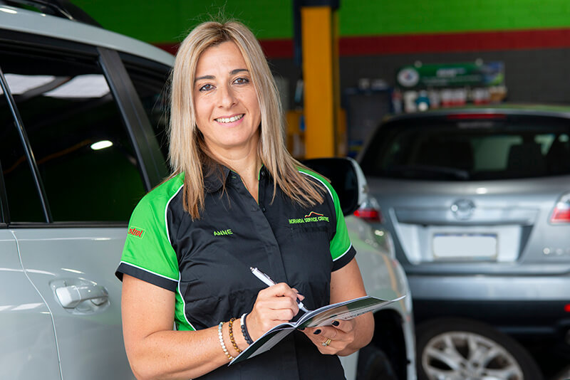 Noranda Service Centre Gallery Images - Co-Owner Anne Working on Logbook and Looking at the Camera