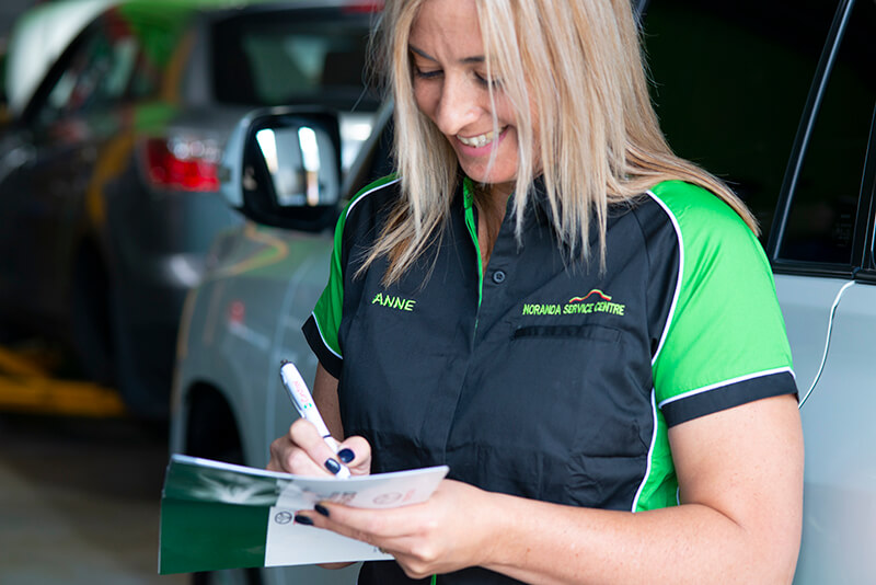 Noranda Service Centre Gallery Images - Co-Owner Anne Working on the Logbook Smiling