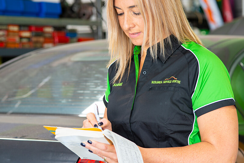 Noranda Service Centre Gallery Images - Co-Owner Anne Working on the Logbook
