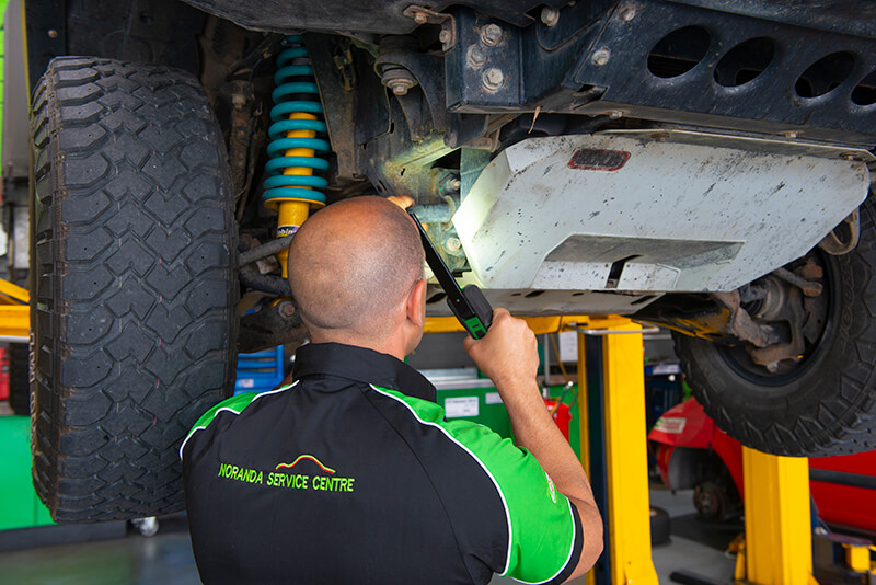 Noranda Service Centre Gallery Images - Mechanic Checking Under the Hood Using Torch