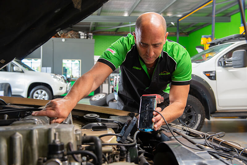 Noranda Service Centre Gallery Images - Mechanic Looking at Interior Vehicle Parts using Mechanic Gadget