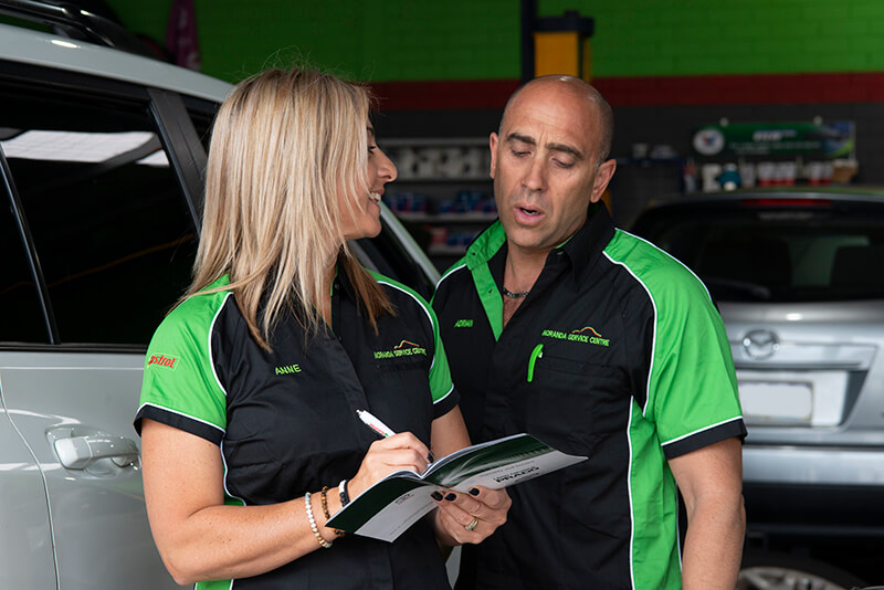 Noranda Service Centre Gallery Images - Mechanic Looking at the Logbook Held by Co-Owner Anne