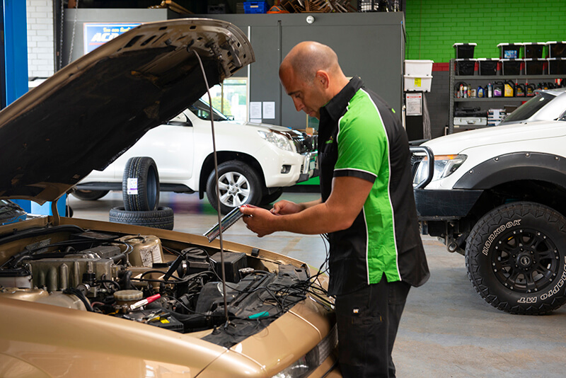 Noranda Service Centre Gallery Images - Mechanic Working on the Car Open Hood