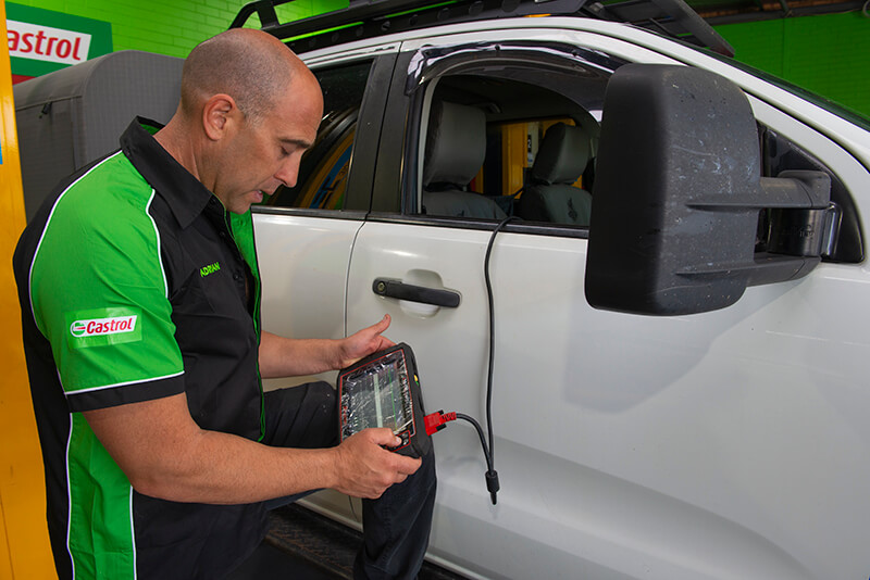 Noranda Service Centre Gallery Images - Servicing White Car with Car Checking Gadget