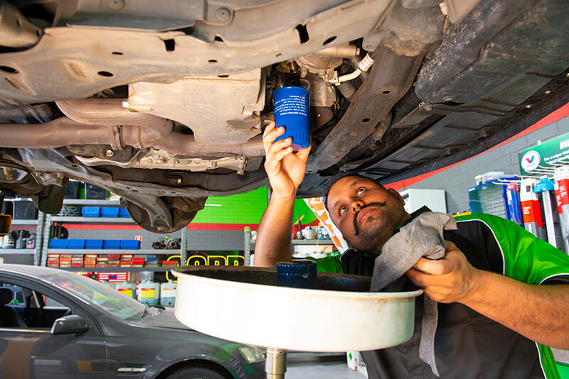Noranda Service Centre Gallery Images - Working on Car Change Oil - Using Canisters to Save Used Oil